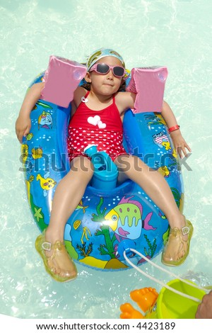 Young child is relaxing in gummiboat in swimming pool.
