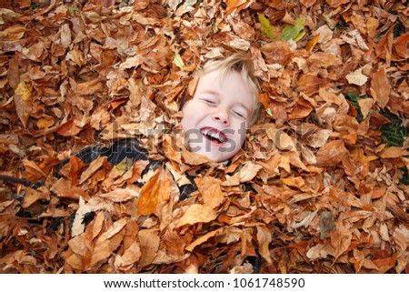 Young child laying buried in a pile of fall leaves laughing with