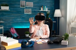 Young child learning lesson course with vr glasses technology gadget at home desk. Smart schoolgirl pupil using vision equipment for elementary school entertainment studying method