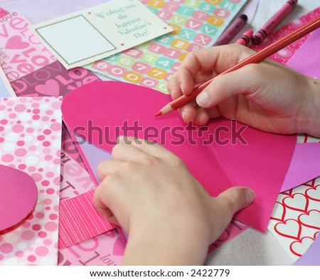 young child making valentine cards