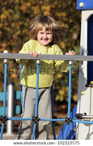 young child playing on colorful playground in autumn