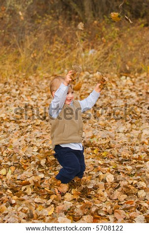 Young child playing with the Autumn leaves
