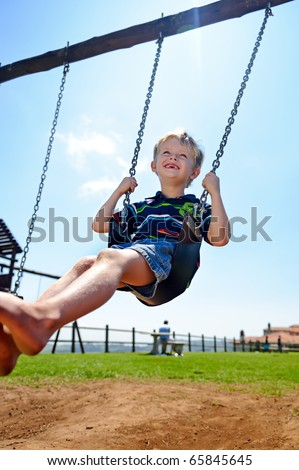 Young child plays on swing in the outdoor playground