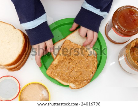 young child's hands making peanut butter and jelly sandwiches