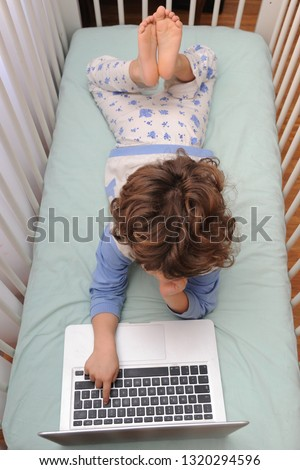 Young child 4 years old in the bed looks lap top computer during n-cov 19 Coronavirus Foto stock ©