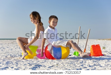 Young children, boy and girl, brother and sister, having fun, playing on a beach with beach balls, buckets and spades