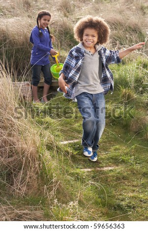 Young Children Carrying Fishing Net At Seaside