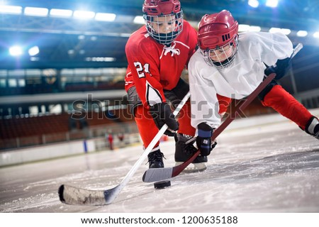young children hockey player handling puck on ice
