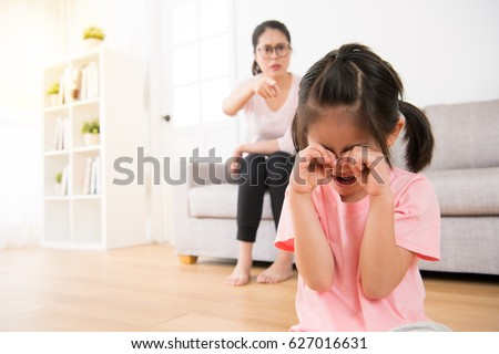 young children making mistakenly crying while kindergarten teacher cursed and teacher pointing to her in the classroom sofa area in the back of the girl blurred background.