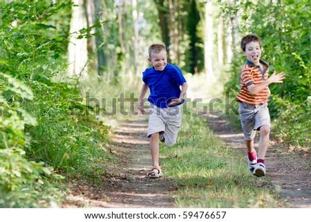Young children running in nature - stock photo