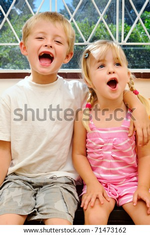 young children shouting for joy with arm around shoulder