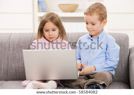 Young children sitting on couch at home, using laptop computer, looking at screen.