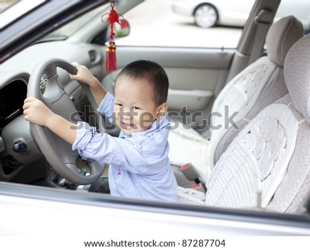 young chinese baby boy playing in the car