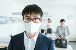 Young Chinese businessman in eyeglasses, protective mask and suit standing in front of camera against his colleagues by desks