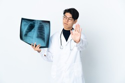 Young Chinese doctor man holding radiography isolated on white background making stop gesture and disappointed