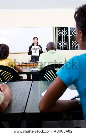 young chinese female teacher teaching chinese to group of adult african student in classroom