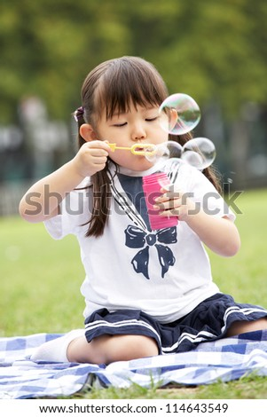 Young Chinese Girl In Park Blowing Bubbles - stock photo