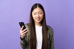 Young Chinese girl using mobile phone over isolated purple background with happy expression