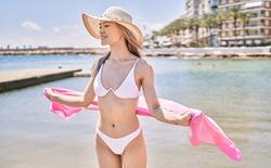Young chinese girl wearing bikini standing at the beach.