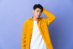 Young Chinese man isolated on purple background with an expression of frustration and not understanding
