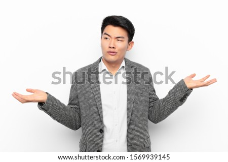 young chinese man shrugging with a dumb, crazy, confused, puzzled expression, feeling annoyed and clueless against flat color wall