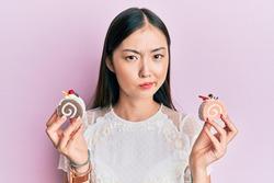 Young chinese woman holding cake sweets skeptic and nervous, frowning upset because of problem. negative person.