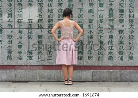 Young chinese woman reading chinese characters on a wall