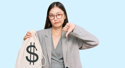Young chinese woman wearing business suit holding dollars bag with angry face, negative sign showing dislike with thumbs down, rejection concept