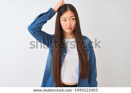 Young chinese woman wearing denim shirt standing over isolated white background confuse and wonder about question. Uncertain with doubt, thinking with hand on head. Pensive concept.