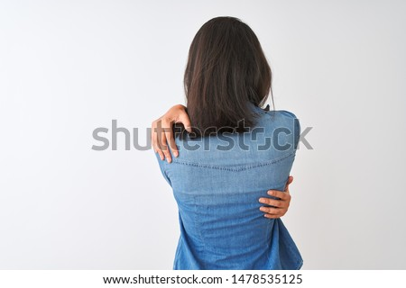 Young chinese woman wearing striped t-shirt and denim shirt over isolated white background Hugging oneself happy and positive from backwards. Self love and self care