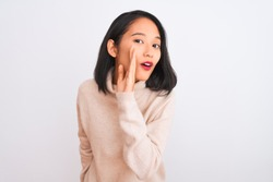 Young chinese woman wearing turtleneck sweater standing over isolated white background hand on mouth telling secret rumor, whispering malicious talk conversation