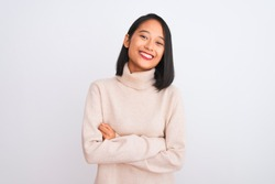 Young chinese woman wearing turtleneck sweater standing over isolated white background happy face smiling with crossed arms looking at the camera. Positive person.