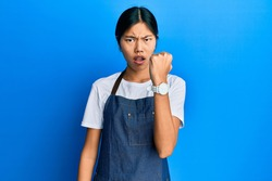 Young chinese woman wearing waiter apron angry and mad raising fist frustrated and furious while shouting with anger. rage and aggressive concept.