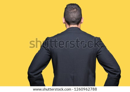 Young Christian priest over isolated background standing backwards looking away with arms on body