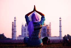 Young christian woman in traditional indian clothes in front of Taj Mahal in Agra, India makes yoga exercises. UNESCO World Heritage Site. Mosque. Mausoleum. Meditation.