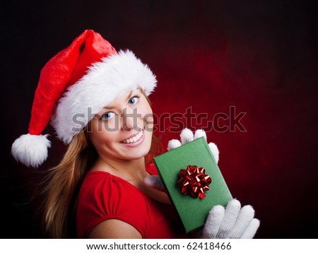 young christmas woman holding present over dark background