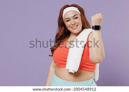 Young chubby overweight plus size big fat fit woman in red top towel warm up training show smart watch with blank black screen isolated on purple background home gym Workout sport motivation concept. Foto stock ©