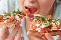 Young chubby woman sitting at table in kitchen binge eating eating slices of pizza fast hungry mouth close-up