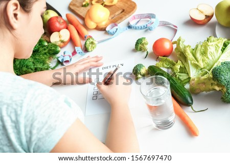 Young chubby woman sitting at table in kitchen with glass of water writing rules of diet plan concentrated back view close-up #1567697470