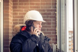 Young civil engineer is having trouble over the phone against brick background. Soft focus, toned.