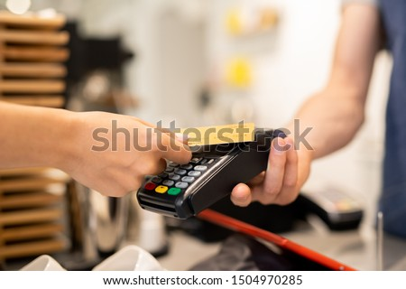 Young client of cafe holding plastic card over electronic payment machine held by waiter or barista while paying for food or drink