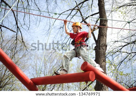 Young climber skilfully go on a suspension bridge in high ropes course.