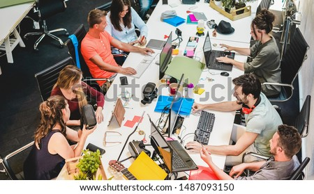Young co-workers team talking during startup - Happy people planning a new project in creative workplace office - Technology, entrepreneur, marketing and concept - Focus on left man with headphones
