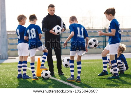 Young coach teaching kids on football field. Trainer explains to schoolboys training rules. Football coach coaching children. Soccer football training session for children. Football tactic education.