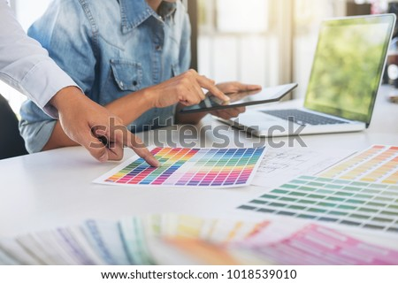 Young colleagues designers working together on a creative project and color samples for selection, Color swatch samples, Brainstorming Planning Partnership, creative graphic design working desktop. #1018539010
