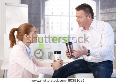 Young colleagues having coffee break, chatting in office.?