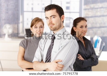 Young colleagues, one man, two women standing in bright office arms crossed, smiling.?