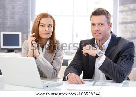 Young colleagues sitting at desk in bright office, working on laptop, smiling. - Shutterstock ID 103558346