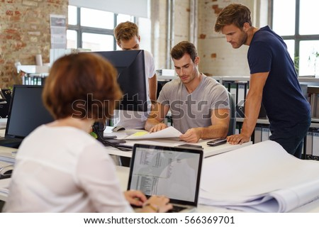 Young colleagues working together in office gathered at desk with computers and papers, with woman with laptop blurred in foreground