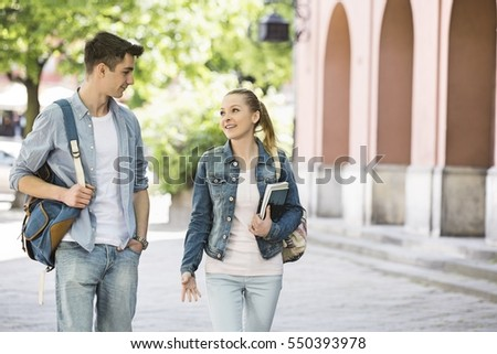 Young college friends talking while walking at campus #550393978